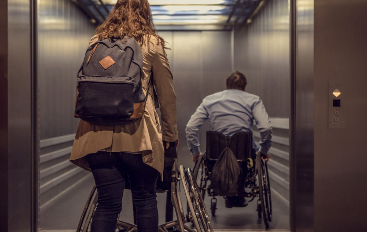 Wheelchair using young man and his girlfriend travelling around a modern city